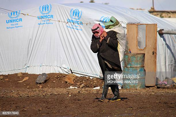 A Syrian man carries a bag on his back as he walks down a muddy path after a storm at a makeshift refugee camp on the outskirts of southeastern...