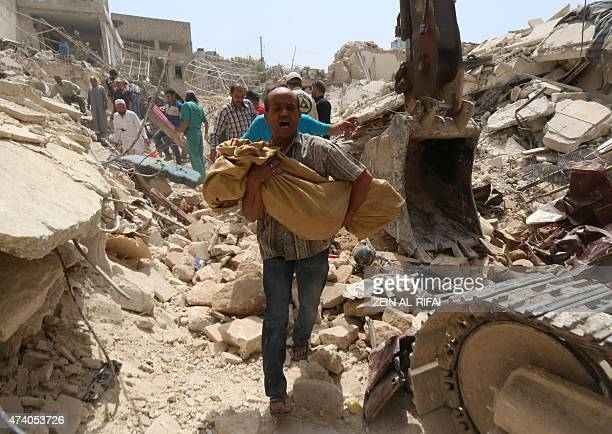 A Syrian man carries a body after it was removed from the rubble of buildings following a reported barrel bomb attack by government forces on the...
