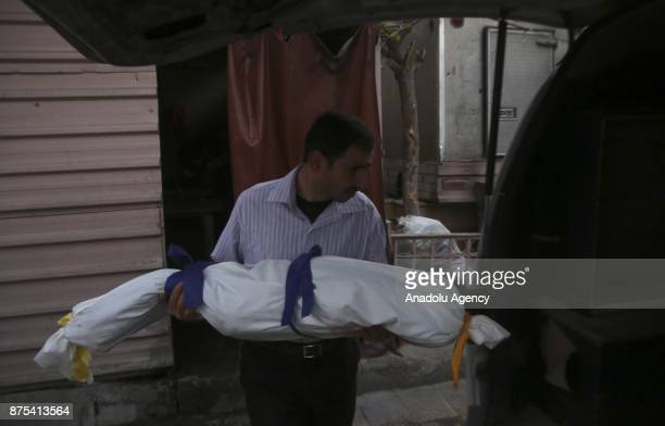 A Syrian man carries a dead body of child after Assad regime's war crafts carry out intensifying airstrikes over residential areas of Douma town of...