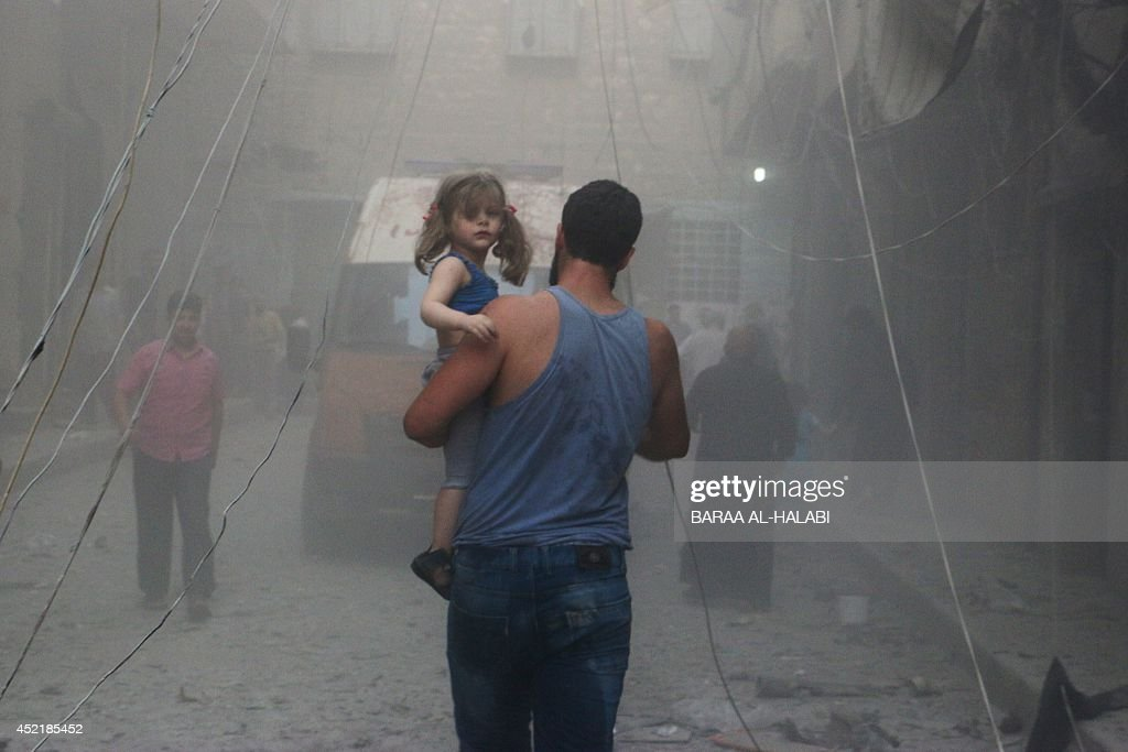 A Syrian man carries a girl on a street covered with dust following a air strike by government forces in the northern city of Aleppo on July 15, 2014. More than 170,000 people have been killed in the three-year war, one third of them civilians, according to the Syrian Observatory for Human Rights.