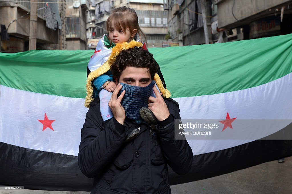 A Syrian man carries a girl on his shoulders as they march in front of a pre-Baath Syrian flag, now used by the Free Syrian Army, during an anti-regime demonstration after the weekly Friday prayers in the Bustan al-Qasr district of the northern city of Aleppo on February 8, 2013. Syrian forces shelled rebel belts, the Syrian Observatory for Human Rights said, as an army offensive raged into a third straight day.