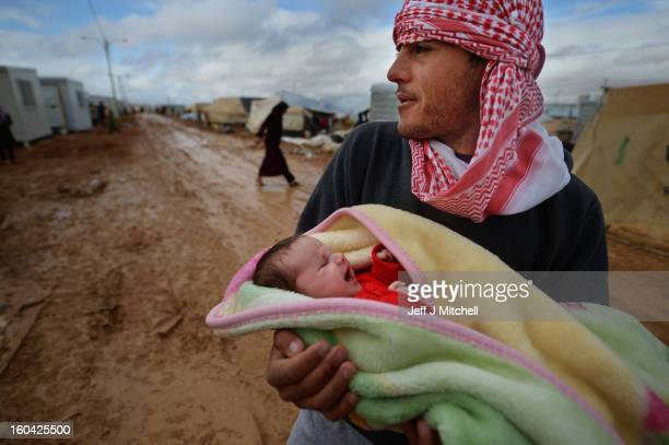 Syrian man carries a newly born child in the Za'atari refugee camp on January 31 2013 in Za'atari Jordan Record numbers of refugees are fleeing the...