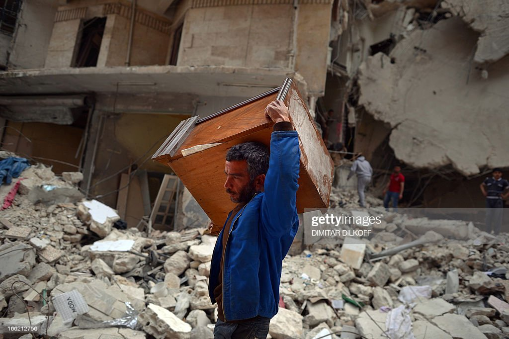 A Syrian man carries a piece of furniture as civilians collect what's left of their belongings from their damaged apartments before fleeing the northern Syrian city of Aleppo on April 10, 2013. The United States is mulling ways to step up support for the Syrian opposition, a top US official said, as US Secretary of State John Kerry and G8 ministers were to meet rebel leaders.