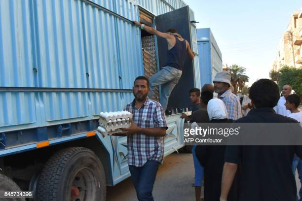 A Syrian man carries a tray of eggs in the eastern Syrian city of Deir Ezzor while food is being delivered on September 11 2017 as Syrian government...