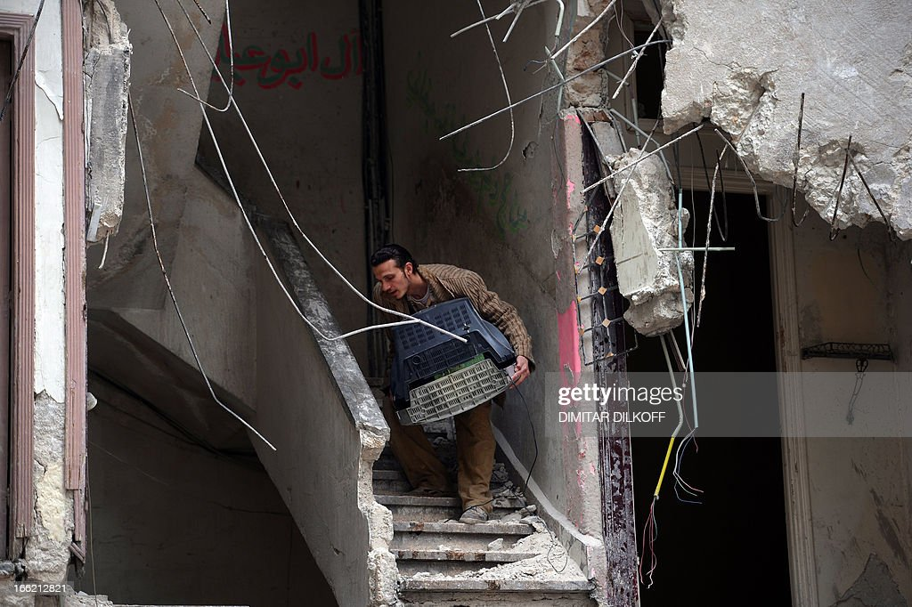 A Syrian man carries a TV as civilians collect what's left of their belongings from their damaged apartments before fleeing the northern Syrian city of Aleppo on April 10, 2013. The United States is mulling ways to step up support for the Syrian opposition, a top US official said, as US Secretary of State John Kerry and G8 ministers were to meet rebel leaders. AFP PHOTO / DIMITAR DILKOFF