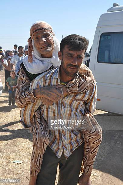 Syrian man carries an old woman as Syrians fleeing from clashes between the Islamic State of Iraq and Levant militants and Democratic Union Party...