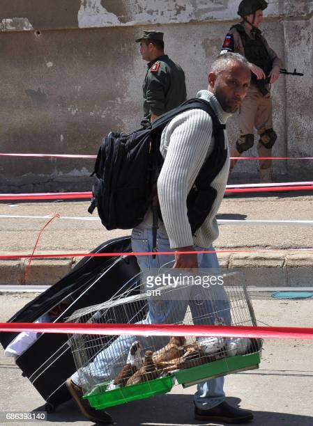 A Syrian man carries cages with birds as opposition fighters and their families arrive at a checkpoint manned by regime forces to be evacuated from...