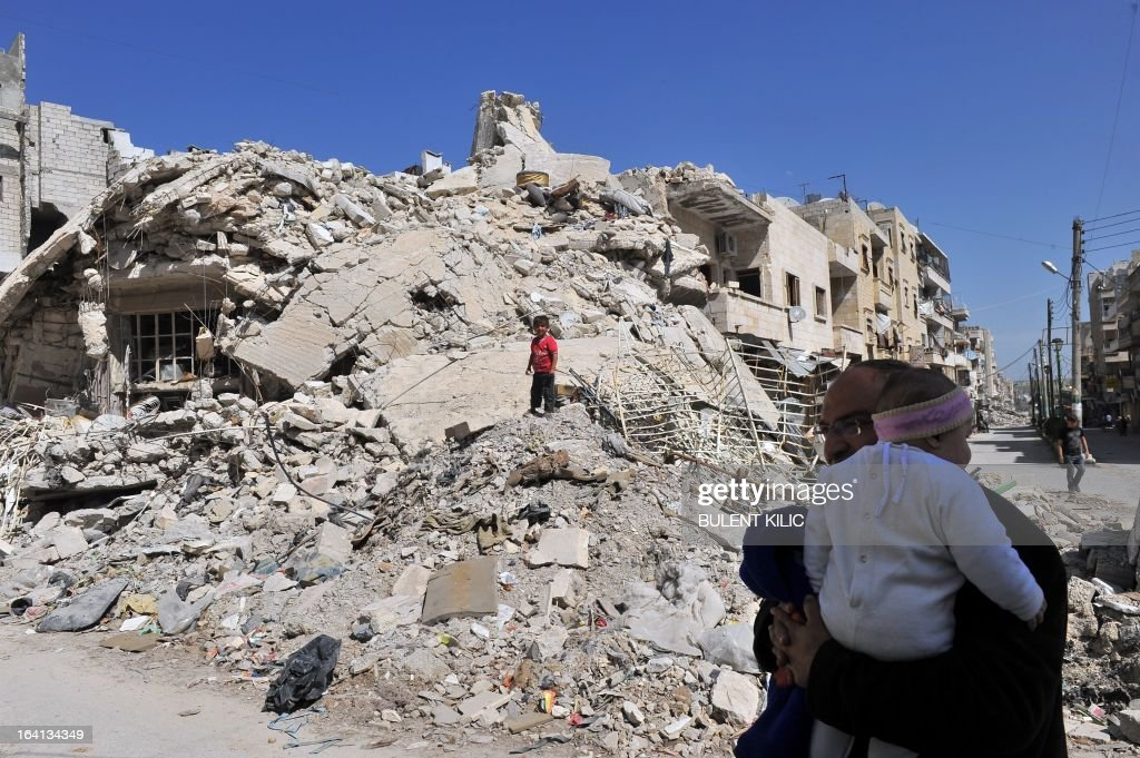 A Syrian man carries his child past damaged buildings in Maarat al-Numan, in the northwestern province of Idlib, on March 20, 2013. The number of Syrian refugees, already past the million mark, could double or triple by the end of the year if no solution is found to the conflict, the UN High Commissioner for Refugees Antonio Guterres said earlier this month.