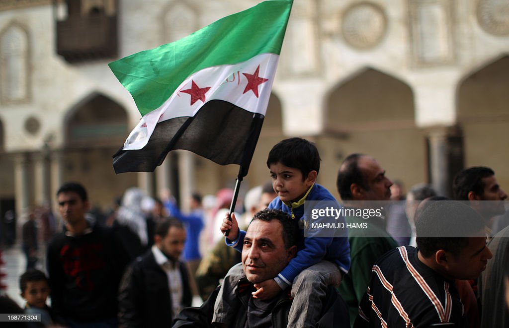 A Syrian man carries his son during a rally in support of the Syrian people and against Syria's President Bashar al-Assad at Al-Azhar mosque in Cairo, on December 28, 2012. Syrian warplanes launched air raids in Damascus province after overnight bombardments and clashes across the country, the Syrian Observatory for Human Rights said.