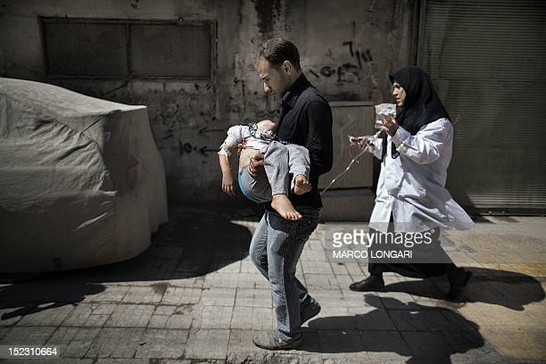 A Syrian man carries his wounded daughter outside a hospital in the northern city of Aleppo on September 18 2012 Syrian troops shelled several...