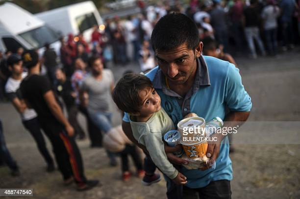A Syrian man carries packaged food as he cradles his child in his arms as they rest beside the highway on their way to the border between Turkey and...
