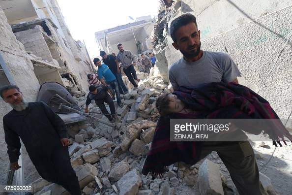 A Syrian man carries the body of a baby after it was recovered from the rubble of a house following a reported bomb barrel attack by Syrian...
