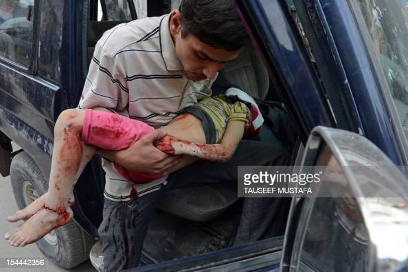 Syrian man carries the body of a boy into a hospital in the northern city of Aleppo on October 20 following shelling by government forces Peace envoy...