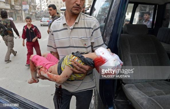 Syrian man carries the body of a boy outside a hospital in the northern city of Aleppo on October 20 following shelling by government forces Peace...