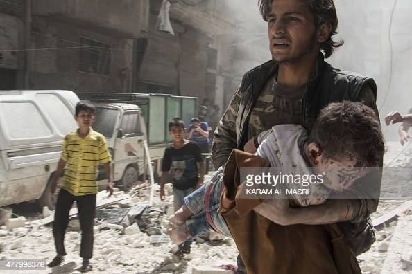A Syrian man carries the body of a child following a reported military strike by government forces in the rebelcontrolled Bustan alQasr district of...