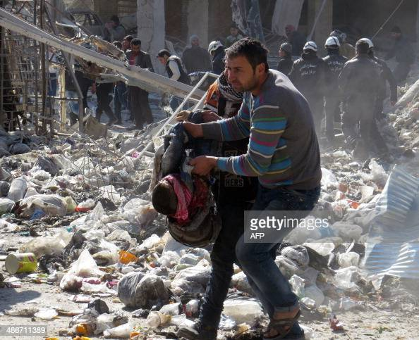 A Syrian man carries the body of a victim out of the rubble of a destroyed building after an alleged air strike by Syrian government forces on the...