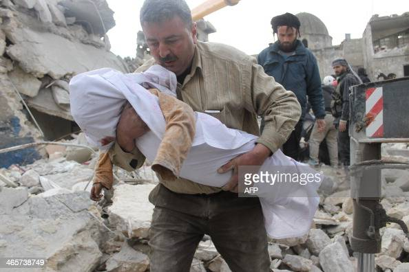 A Syrian man carries the body of a victim out of the rubble of a destroyed building following alleged air raids by government forces on the...