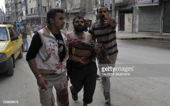 A Syrian man carries the body of his fiveyearold son Mohammed Mustafa outside a hospital following shelling by Syrian government forces during battle...