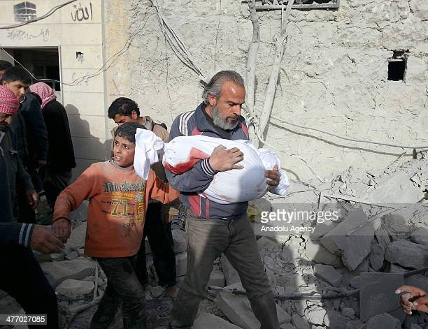 Syrian man carries the dead body of a child after a barrel bomb attack dropped by Syrian regime helicopters on the oppositioncontrolled AlSahur...