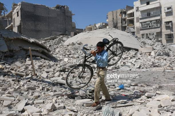 A Syrian man carrying a bicycle makes his way through the rubble of destroyed buildings following a reported air strike on the rebelheld Salihin...