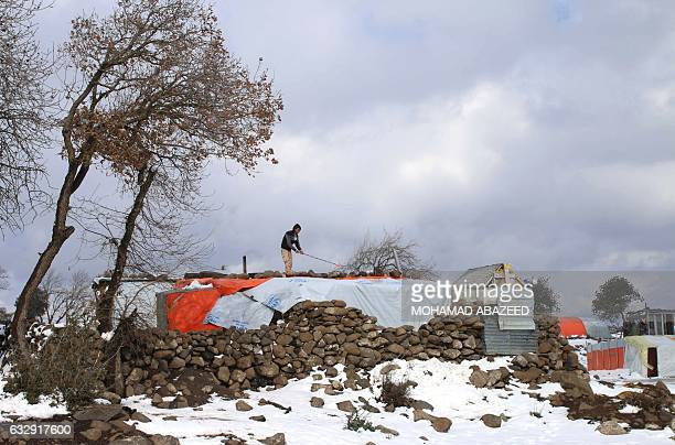 A Syrian man clears snow from the roof of his tent after a storm at a makeshift refugee camp near the village of Burayqah on the outskirts of...