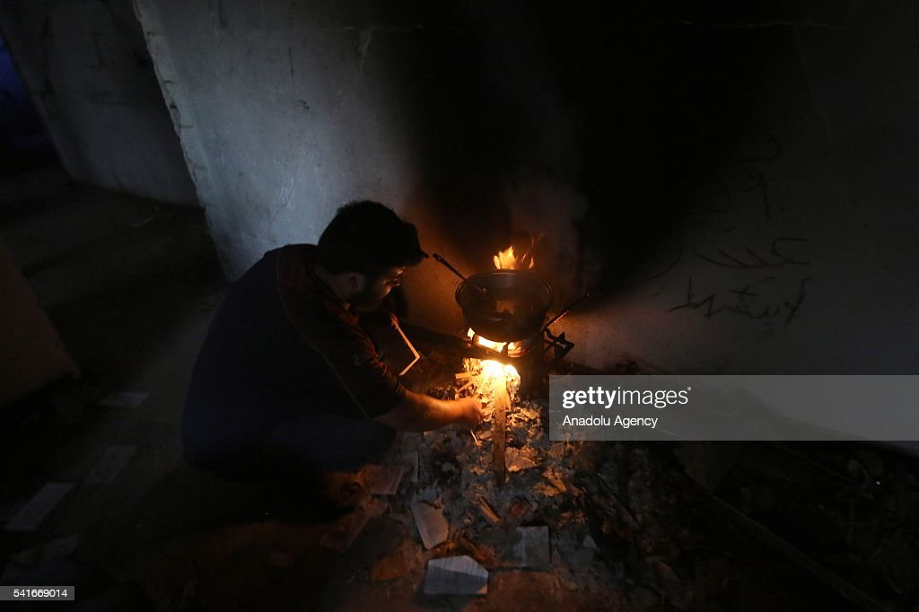 Syrian man cooks for Iftar during the Islamic holy month of Ramadan at Cobar district of eastern Goutha despite the airstrikes of Syrian regime...