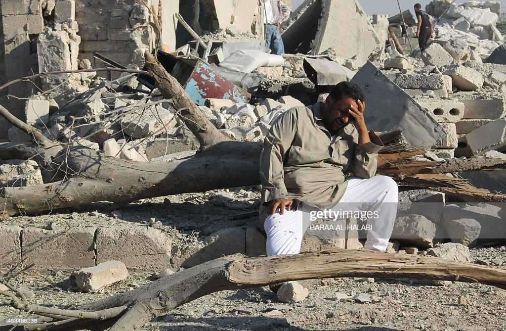 A Syrian man cries as he sits on the rubble of a building following a reported barrelbomb attack by Syrian government forces on August 11 2014 in the...