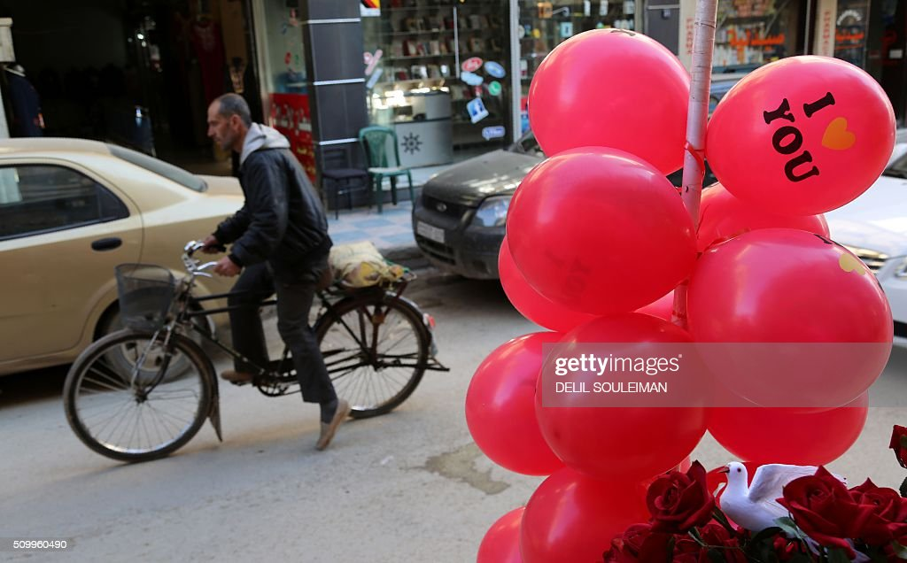 A Syrian man cycles past red flowers and balloons as shops display Valentine's day gifts in the northeastern city of Qamishli on February 13, 2016. / AFP / DELIL SOULEIMAN