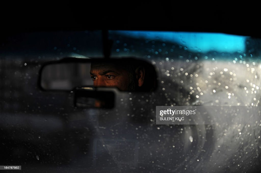 A Syrian man drives a car in the center of the northern Syrian city of Aleppo on March 28, 2013. More than 70,000 people have died in Syria's two-year conflict, the UN says. AFP PHOTO/BULENT KILIC