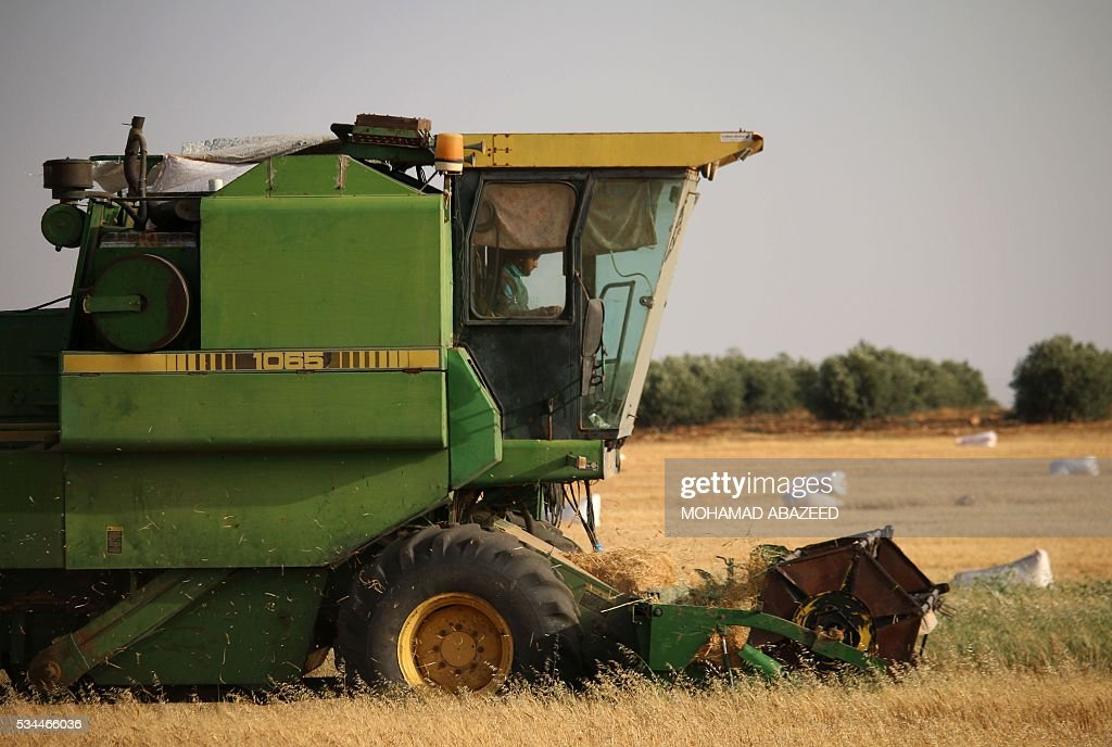 A Syrian man drives a combine harvester as they harvest wheat in rebel-held area of Daraa, in southern Syria, on May 26, 2016. Most of Daraa province is controlled by opposition forces, though the government holds parts of the provincial capital and a few villages in the northwest. ABAZEED