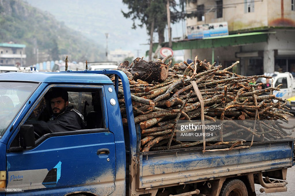 Syrian man drives a pick-up truck loaded with chopped wood in the northern town of Darkush on January 23, 2013. Beset by a freezing winter and stifling fuel and electricity shortages, Syrian civilians desperate to stay warm in a northern forest have no choice but to cut down trees for firewood. Once a tourist destination for Syrians and other Arabs across the Middle East, the formerly pristine national park to the north and west of the city of Idlib is being systematically stripped bare.