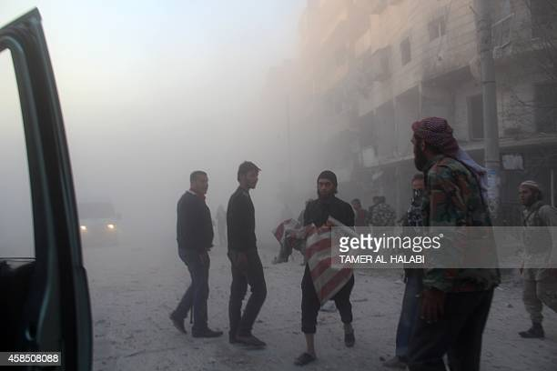 A Syrian man evacuates a body following a reported barrel bomb attack by government forces in the AlMuasalat area in the northern Syrian city of...