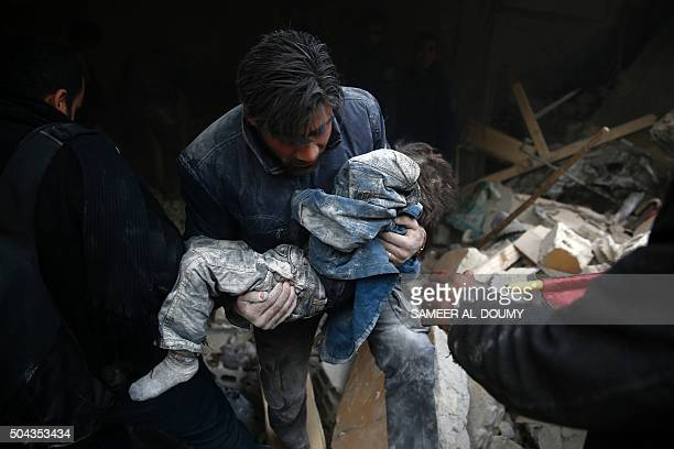 Syrian man evacuates a child from the rubble of a destroyed building following air strikes on the Eastern Ghouta town of Douma a rebel stronghold...