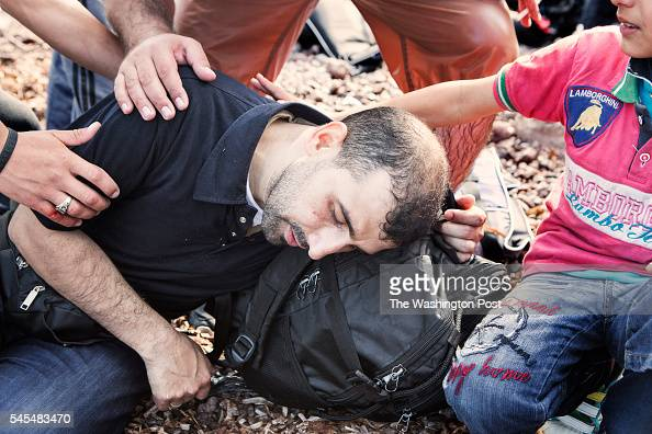 Syrian man falls ill upon arriving after drinking too much sea water on August 1 2015 on the island of Lesvos Greece