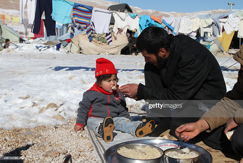 A Syrian man feeds his child in the Arsal refugee camp in the Lebanese Bekaa valley on December 15, 2013. Thousands of Syrian refugees living in makeshift camps in Lebanon were weathered a winter storm that brought snow, rain and freezing temperatures to the country.