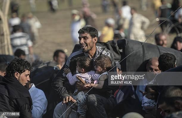 A Syrian man fleeing the war carries children through broken down border fences to enter Turkish territory illegally near the Turkish border crossing...