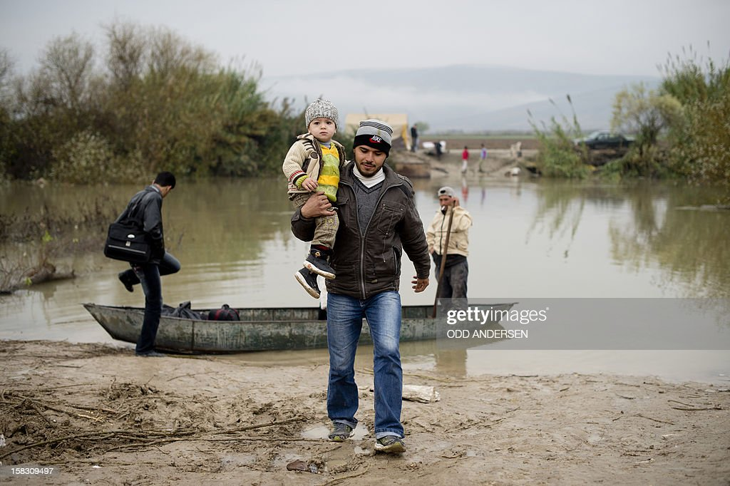 A Syrian man from Jisr al-Shughur carries his son as a family gets ready to board a boat to flee across the Orontes river to Turkey near the northern Syrian town of Darkush on December 13, 2012. The number of Syrian refugees registered in neighbouring countries and North Africa has passed half a million, the UN's refugee body said, adding that many more have not come forward to seek help.