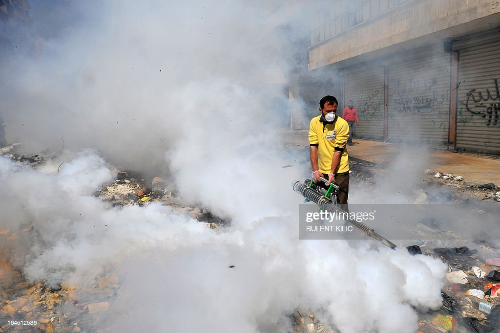 A Syrian man fumigates a street covered with uncollected garbage in the northern city of Aleppo on March 24, 2013. Syria's mainstream insurgent Free Syrian Army does not recognise Ghassan Hitto, a rebel prime minister chosen by dissidents after hours of heated talks last week, a rebel official told AFP.