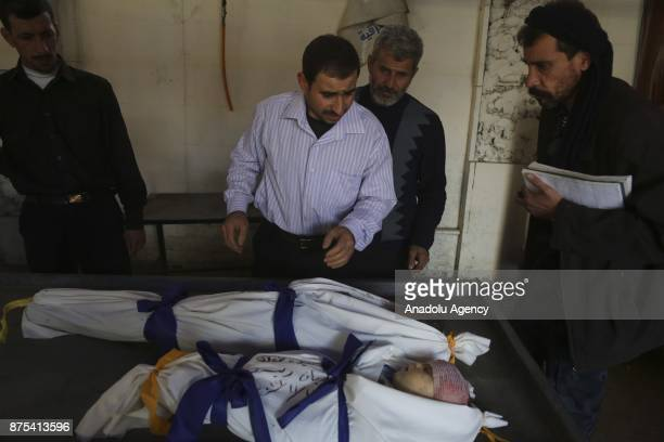 A Syrian man gestures as he looks at the dead bodies of children after Assad regime's war crafts carry out intensifying airstrikes over residential...