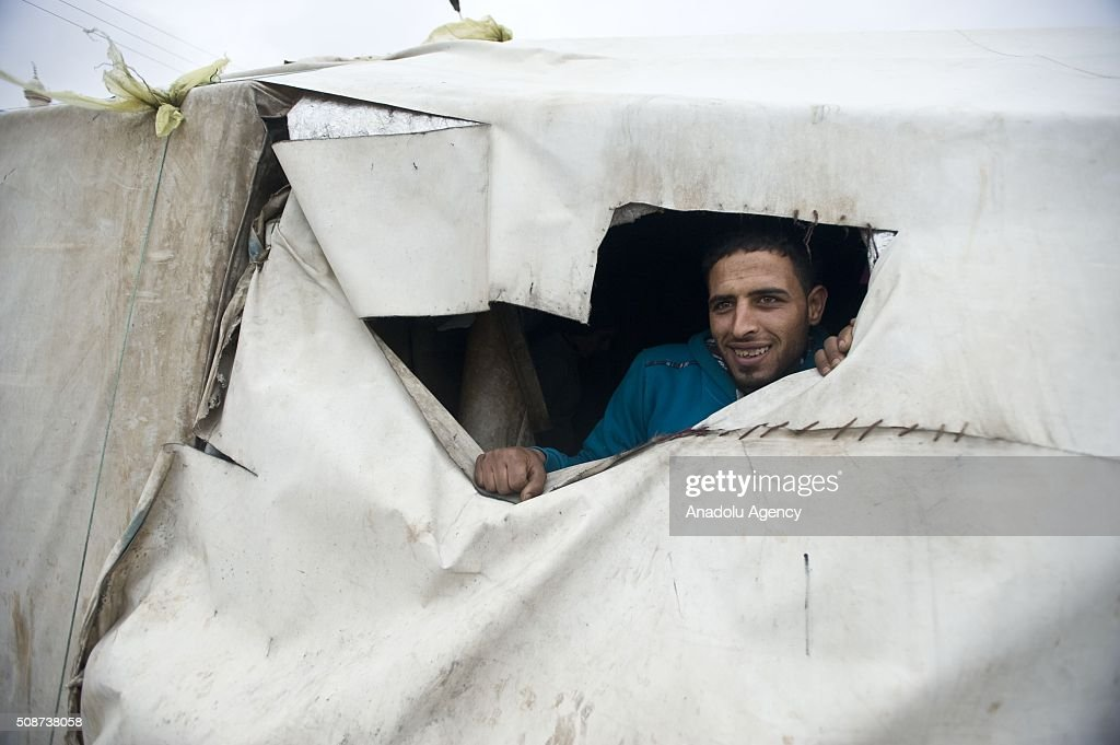 A Syrian man gestures as he looks out from his tent at tent city built by IHH Humanitarian Relief Foundation near the Bab al-Salam border gate on Turkey's border in Azez district of Aleppo as they flee to Turkey to escape heavy Syrian regime and Russian airstrikes, on February 6, 2016.
