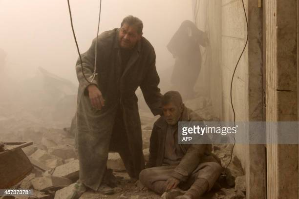 A Syrian man helps an injured man following an airstrike in Aleppo's Maadi neighborhood on December 17 2013 Two children were among at least 13...