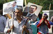 A Syrian man holding up portraits of President Bashar alAssad and his Russian counterpart Valdimir Putin joins several hundred people who gathered...