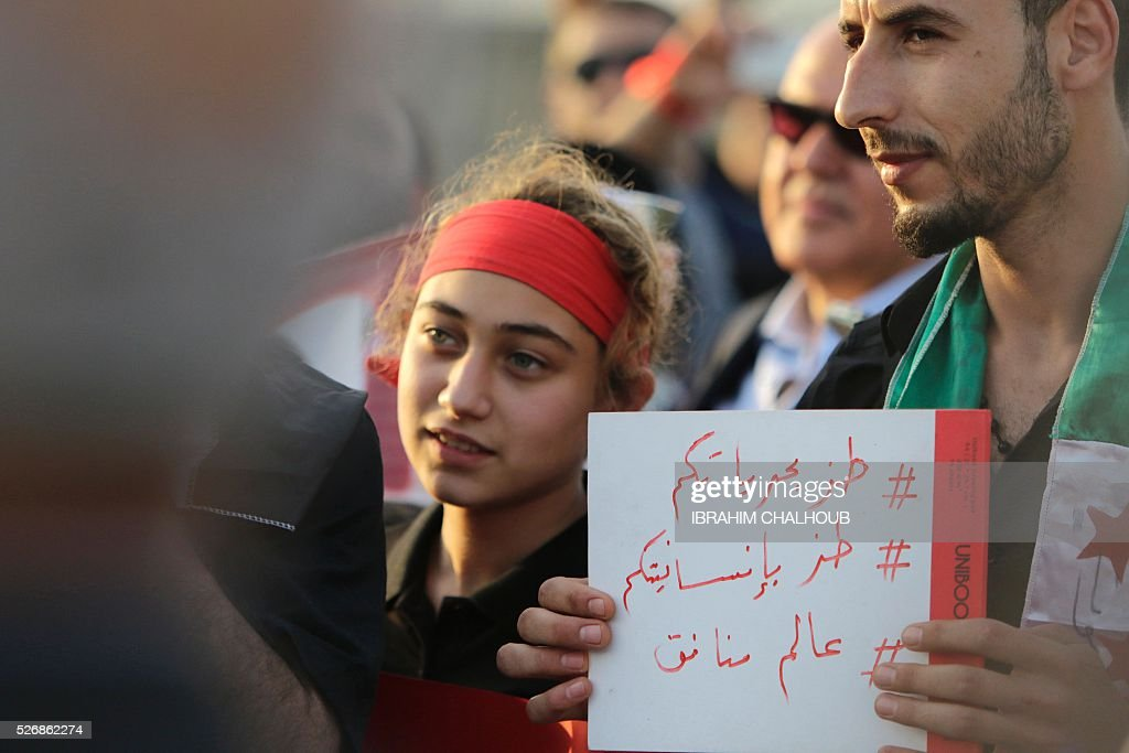 A Syrian man holds a placard during a rally in solidarity with Aleppo, in the Lebanese northern port city of Tripoli, on May 1, 2016. More than a week of fighting in Syria's second city has killed hundreds of civilians and left a UN-backed peace process hanging by a thread. Concern has been growing that the fighting in Aleppo will lead to the complete collapse of a landmark ceasefire between President Bashar al-Assad's regime and non-jihadist rebels that was brokered by Moscow and Washington. / AFP / IBRAHIM