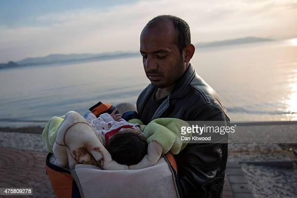 Syrian man holds his child aftre after being escorted into the harbour by the Greek Coastguard who found them drifing offshore on June 04 2015 in Kos...
