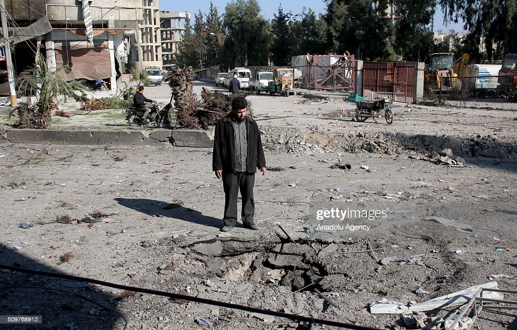 A Syrian man inspects the area after Assad regime war crafts carried out an airstrike over Eastern Ghouta region in Damascus, Syria on February 12, 2016.