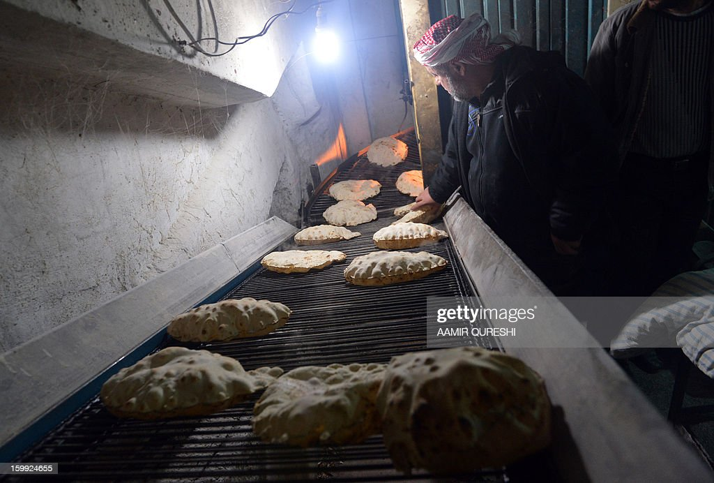 A Syrian man inspects the bread at a rebel-run bakery in Jabal al-Akrad region, northeast of Latakia province, late January 22, 2013. Several flashpoints in Syria's conflict, chiefly Damascus and Aleppo in the north, have been struck by a severe bread shortage and a lack of fuel used for cooking, heating and transportation.