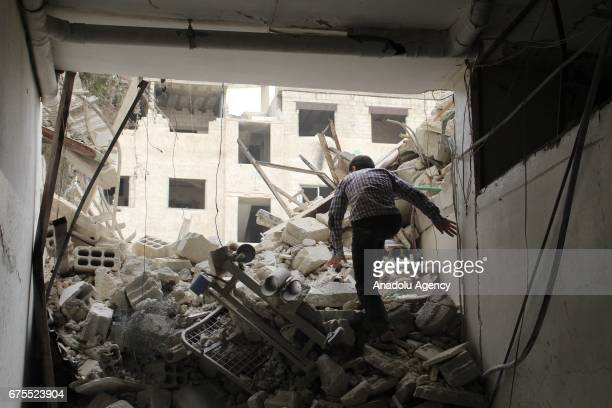 Syrian man inspects wreckage of collapsed Arbin hospital after Assad Regime's airstrike hit residential areas at the Arbin district of Eastern Goutha...