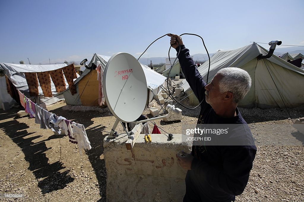 "A Syrian man installs a satellite TV system at the entrance of his tent at a refugee camp in the village of al-Marj in the Bekaa valley on March 6, 2013. The number of Syrians who have fled their war-ravaged country and are seeking assistance has now topped the 1 million mark, the UN refugee agency said, warning that Syria is heading towards a ""full-scale disaster."" AFP PHOTO/JOSEPH EID"