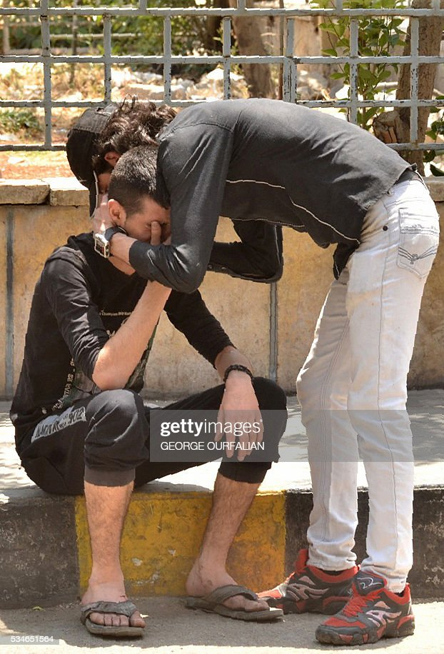 A Syrian man is comforted as he mourns following shelling on the government-held Meidan neighbourhood, which is historically an Armenian area, of the northern Syrian city of Aleppo, on May 27, 2016. OURFALIAN