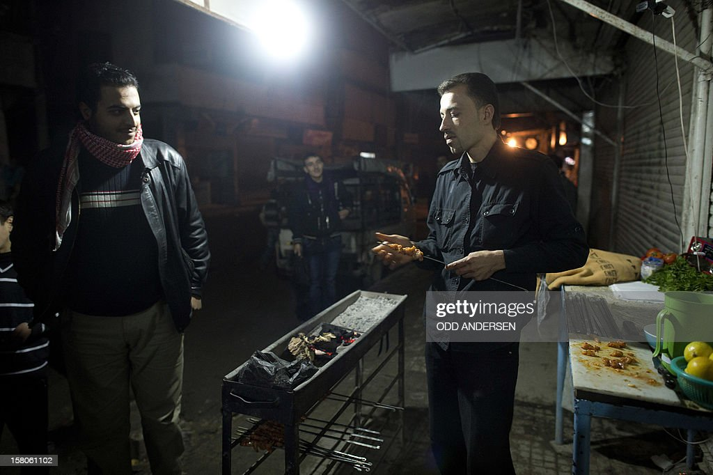 A Syrian man is offering charcoal grilled kebabs under his battery powered light bulb in the main street of the Aleppo neighbourhood of al-Fardos on December 9, 2012. Al-Fardos, a traditionally poor but bustling community with it's inhabitants crowding shops and cafes after dark, is slowly seeing some of the shops reopening after the frontlines has moved to other areas of the city. But with Aleppo being completely cut of from power and water supply the town is completely black after nightfall apart from passing cars and a few generators running in reopened businesses. AFP PHOTO / ODD ANDERSEN